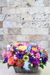 Seramik ayakkabıda kırmızı güller ve beyaz lilyumlardan aranjman ile sevginizin masumluğunu gösterin.