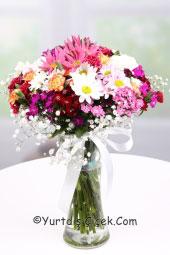 Cam vazoda rengarenk kır çiçeklerinden hazırlanan buket ile yurtdışına çiçek gönderebilir ve ona unutulmaz olduğunu gösterebilirsiniz.