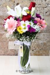 Cam vazoda 3 kırmızı gül, 1 dal lilyum ve kır çiçeklerinin renklerinden hazırlanan buket ona olan sevginizi haykıracak. Yaklaşık Ürün Boyutu : 45 cm