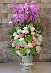 Pembe kutuda mor orkide ve kır çiçekleri ile hazırlanan tasarım sevdiklerinizi mutlu etmeye yetecektir.